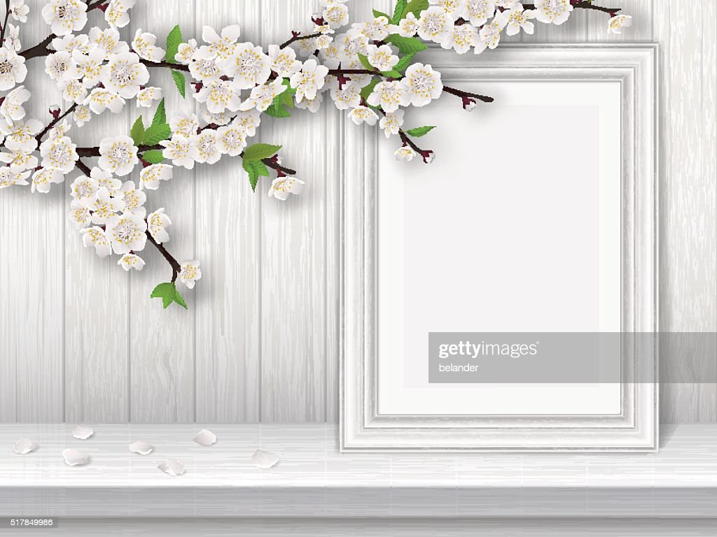 Spring blooming cherry branch and photo frame on white table