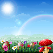 Spring Easter background. Easter eggs in grass with flowers and red mushroom