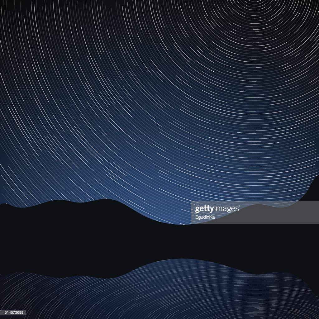 Star trails in the night sky and rocks