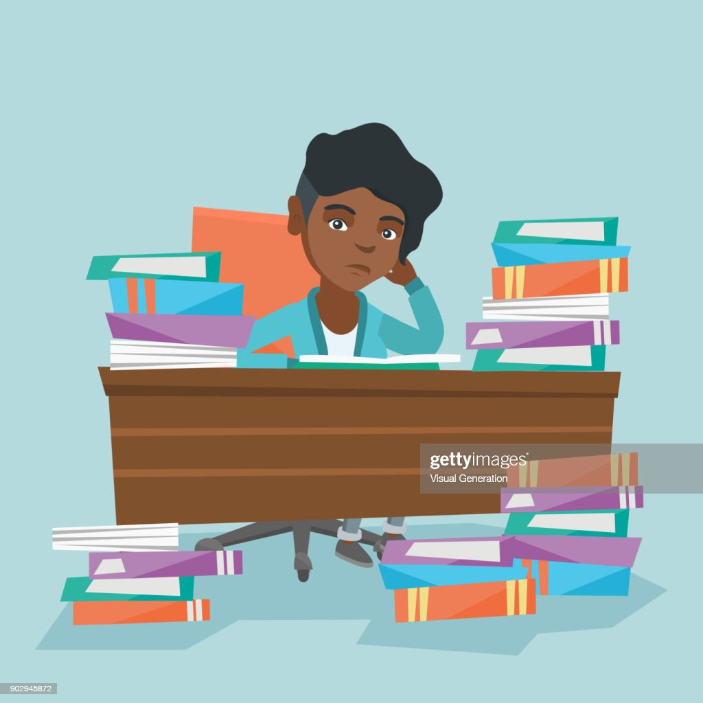 Student sitting at the table with piles of books