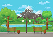 Summer day in the park . Benches, trash cans and street lamp on an asphalt park trail with lush green trees and bushes. Mountains, lake and blue sky with clouds on the background.
