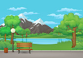 Summer day in the park. Wooden bench, trash can and street lamp on an asphalt park trail with lush green trees and bushes. Green meadow, lake or river, mountains and blue sky with clouds in the background.