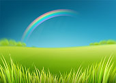 Summer meadow field with rainbow after rain. Nature background with green grass