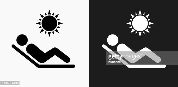 sunbathing icon on black and white vector backgrounds - lying down stock illustrations
