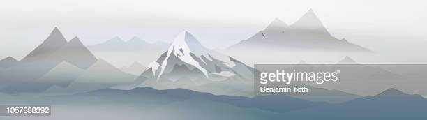 sunrise in snow covered mountains landscape with fog panorama - fog stock illustrations
