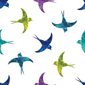 Swallow silhouettes with colorful watercolor fill seamless pattern