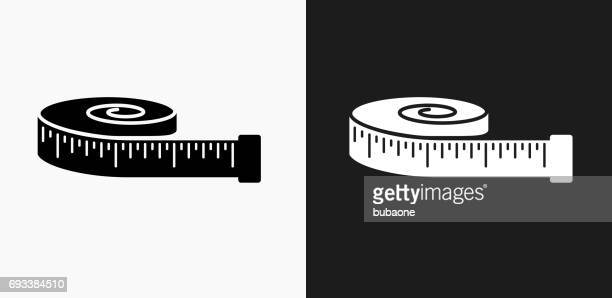tape measure icon on black and white vector backgrounds - tape measure stock illustrations, clip art, cartoons, & icons