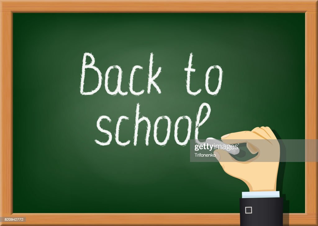 Teacher is writing chalk on the blackboard.