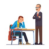 Teacher looking at a sleeping teen student