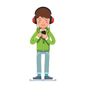 Teen boy in headphones listening to music on phone