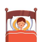 Teen boy sleeping peacefully smiling in her bed