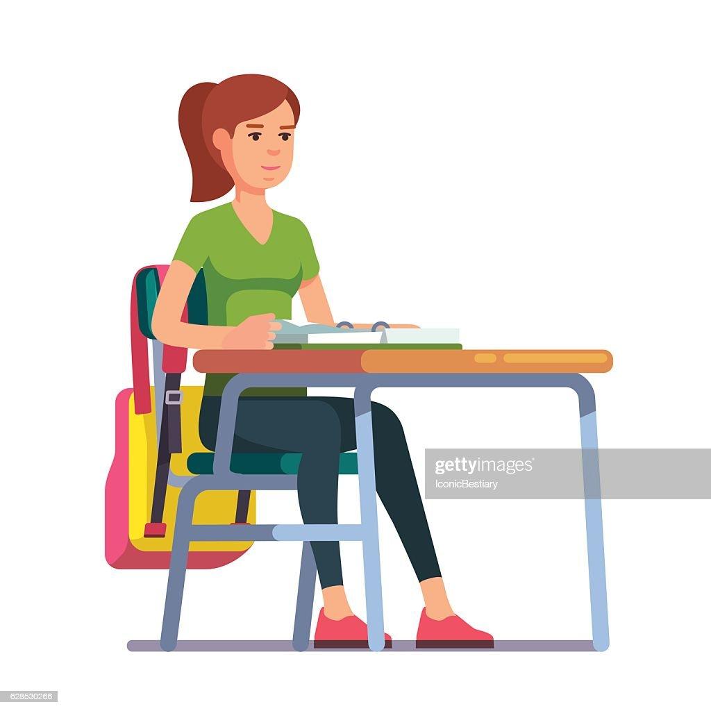 Teen student girl sitting at her school desk