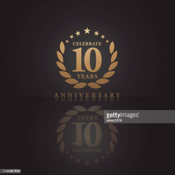 ten years golden anniversary icon with dark color background - anniversary stock illustrations