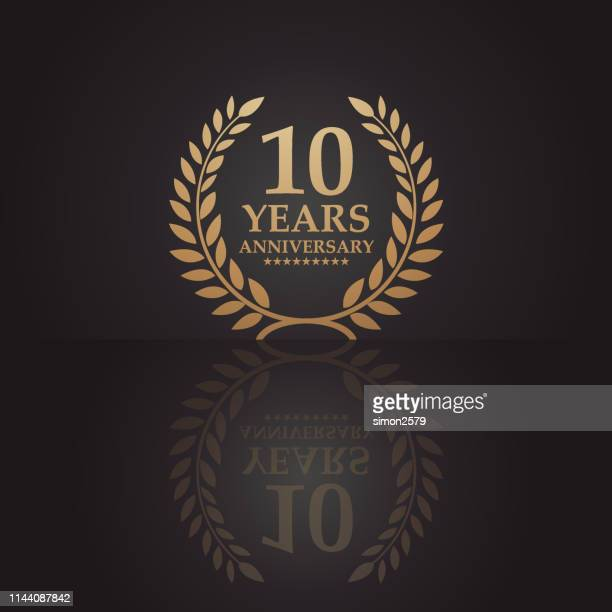ten years golden anniversary icon with dark color background - insignia stock illustrations