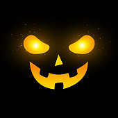 Terrible Halloween face. Yellow glowing eyes with flying magical dust. Cartoon scary face on a black background. Vector illustration. EPS 10