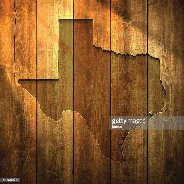 texas map on lit wooden background - texas stock illustrations