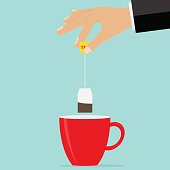 The hand holds a teabag over the cup. Brew tea