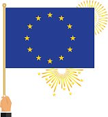 The hand holds the flag of the European Union. Flag of the European Union in hand