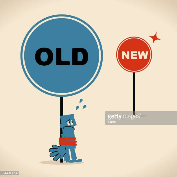 The new and the old way, businessman is tied up with the old sign, concept about bureaucracy or old habit, addiction, old thought pattern