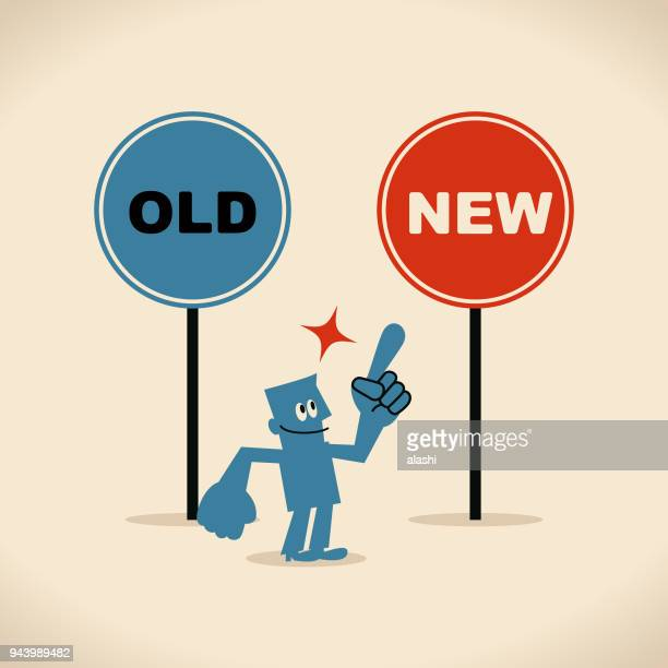 The new and the old way, smiling businessman pointing at the new sign by index finger