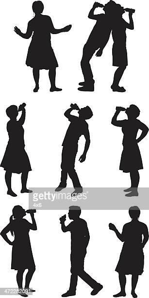 Sedento homens e mulheres beber garrafas de água