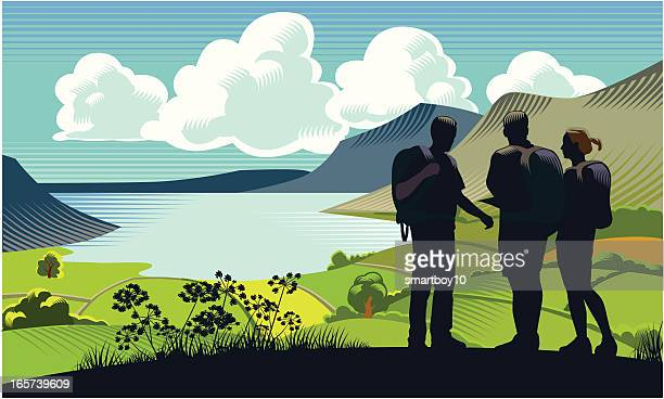 Three backpackers by a lake near mountains and green grass