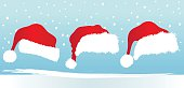 Three Different Santa Hats And Winter Background
