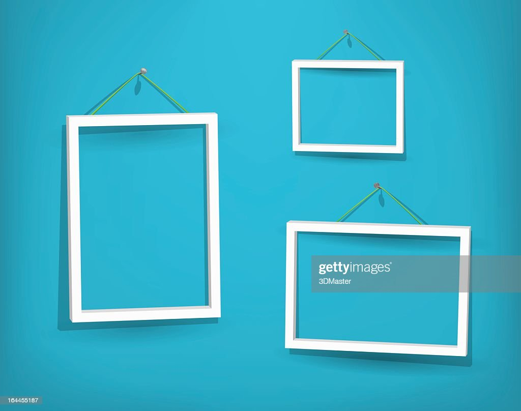 Three empty white frames on the wall