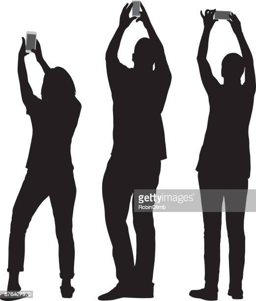 illustrazioni stock, clip art, cartoni animati e icone di tendenza di three people taking pics with smart phones - stare in piedi