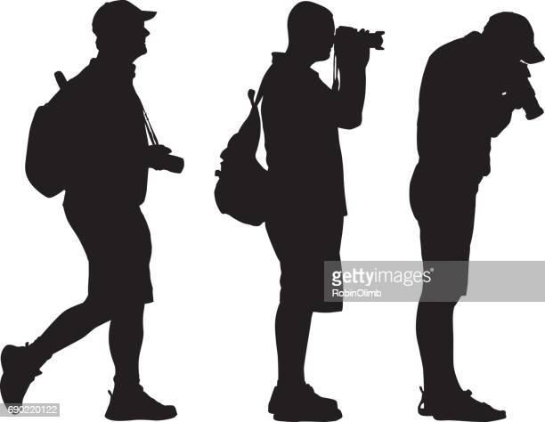 three photographer silhouetts - camera stand stock illustrations, clip art, cartoons, & icons