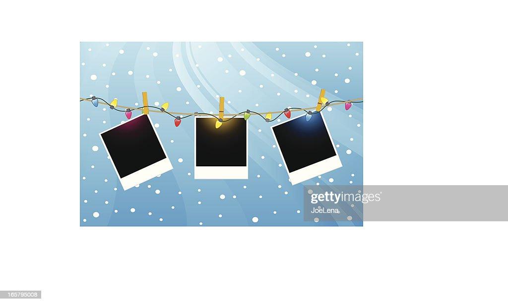 Three Polaroids hanging from Christmas lights