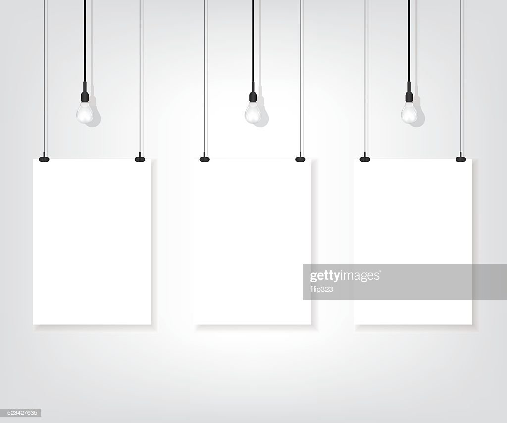 Three white poster on wall and bulb