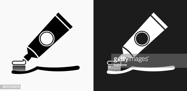 tooth brush and paste icon on black and white vector backgrounds - toothpaste stock illustrations