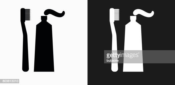 toothbrush and paste icon on black and white vector backgrounds - toothpaste stock illustrations
