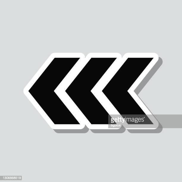 左を指す三重のシェブロン。灰色の背景にアイコンステッカー - 山形模様点のイラスト素材/クリップアート素材/マンガ素材/アイコン素材