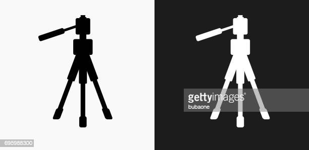 tripod icon on black and white vector backgrounds - camera tripod stock illustrations, clip art, cartoons, & icons
