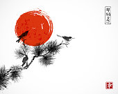Two birds on pine tree branch and big red sun. Traditional oriental ink painting sumi-e, u-sin, go-hua.  Hieroglyphs - zen, freedom, nature, happiness