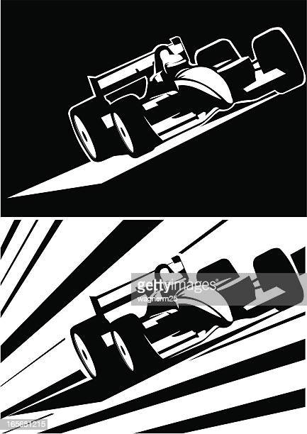 Two black and white formula one cars running