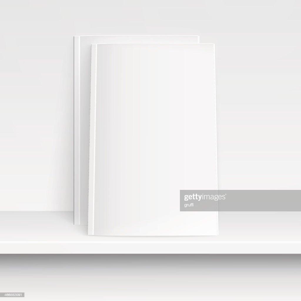 Two blank white magazines on shelf..