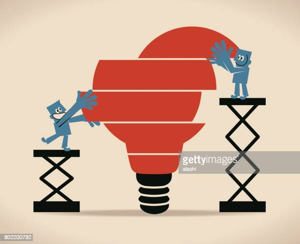 Two Businessman standing on ladder, completing an idea light bulb puzzle