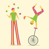 Two circus or street performers, one stilt walker juggling and one doing a handstand on a unicycle.