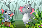 Two elephants in the forest with dry tree branches background
