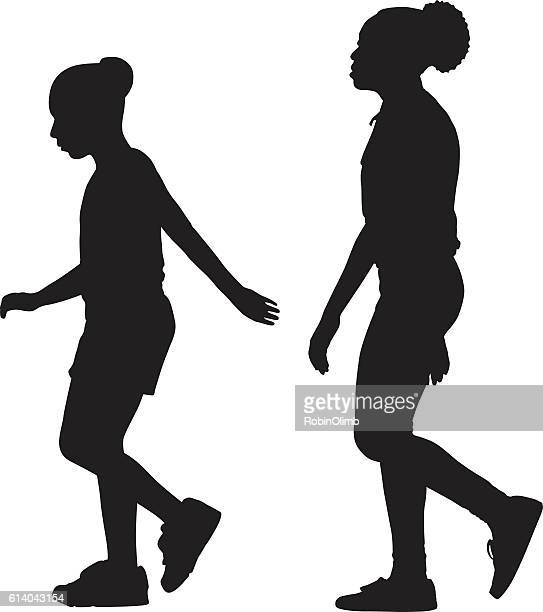 two girls walking together sihouette - ethnicity stock illustrations
