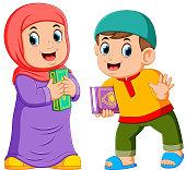 Two kids holding holy Qoran