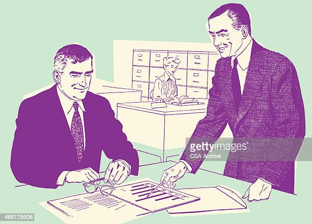 Two Men Discussing a Document at Office Desk