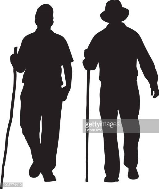 two men hiking silhouettes - walking cane stock illustrations