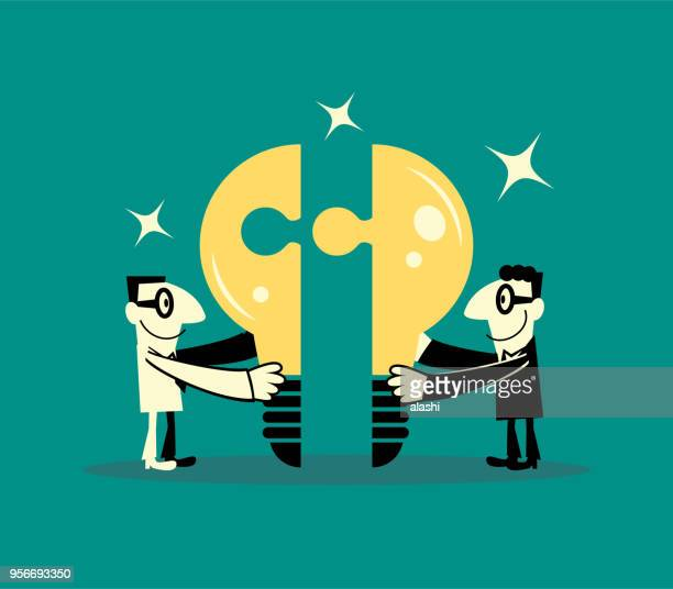 Two smiling businessmen completing idea light bulb jigsaw puzzle (teamwork)