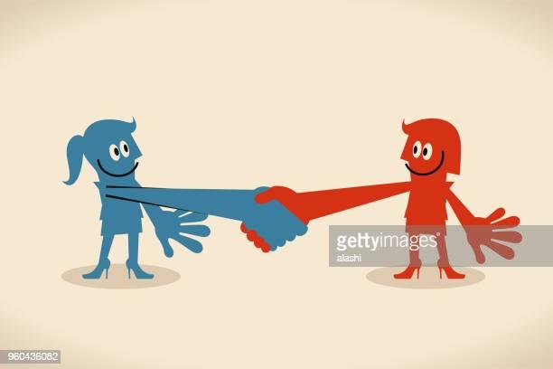 Two smiling businesswomen shaking hands