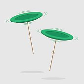 Two spinning green plates on brown pole