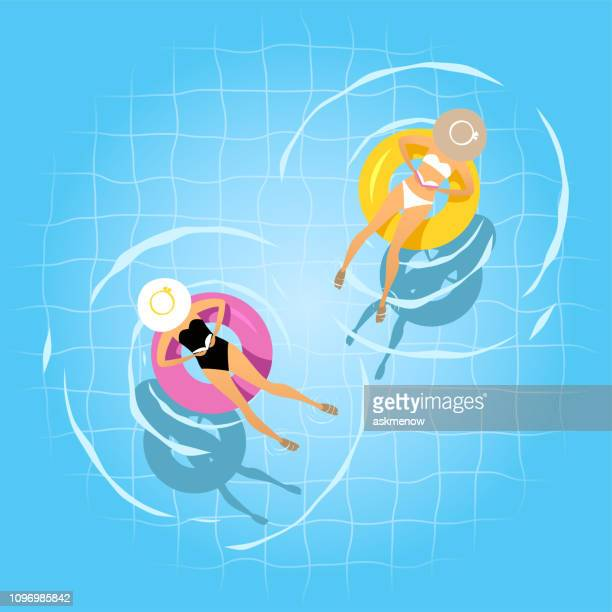 two women swimming on the inflatable ring - floating on water stock illustrations